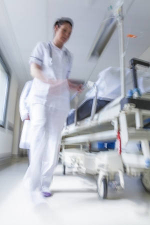 emergency room: A motion blurred photograph of a patient on stretcher or gurney being pushed at speed through a hospital corridor by doctors & nurses to an emergency room