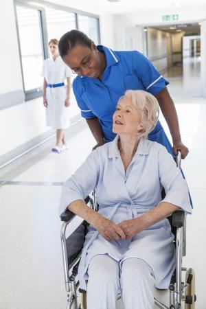 Senior female woman patient in wheelchair sitting in hospital corridor with African American female nurse Standard-Bild