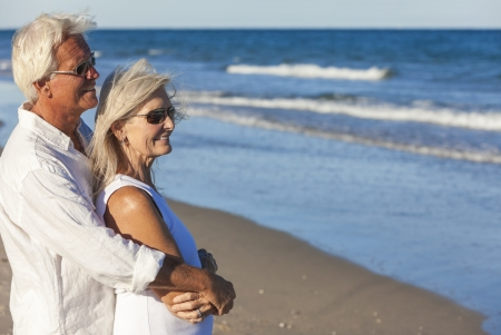 happy retirement: Happy senior man and woman couple together wearing sunglasses & looking out to sea on a deserted tropical beach with bright clear blue sky Stock Photo