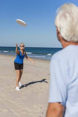 concave: Fit and healthy senior man woman couple playing with concave plastic disk on a deserted beach by the sea