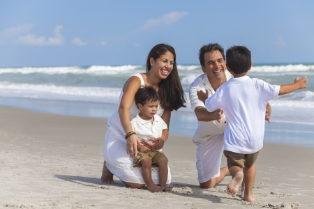 A happy family of mother, father parents & boy son children, playing and having fun on a sunny beach Standard-Bild
