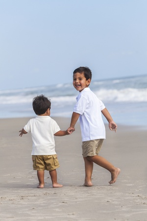 Two happy young hispanic boy children brothers playing together on a beach photo