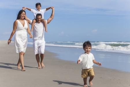 hispánský: Šťastný hispánský rodiny matka, otec rodiče a dva chlapce syn děti, playng a baví ve vlnách slunné pláži Reklamní fotografie