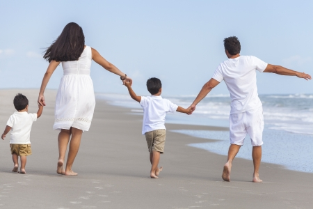 Rear view of happy family of mother, father and two children, boy sons, walking holding hands and having fun in the sand on a sunny beach photo