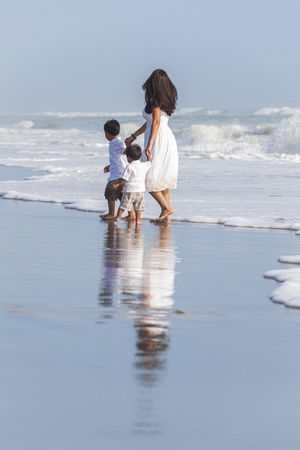 single mother: A family of single mother and two boy children sons holding hands in the waves of a sunny beach