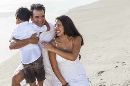 A happy family of mother, father parents & boy son child, playng and having fun in the waves of a sunny beach