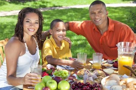 familia comiendo: A, sonriendo Familia afroamericana feliz, padre, madre e hijo comer alimentos saludables en una mesa fuera, el padre cumple un jugo de naranja para el niño. Foto de archivo