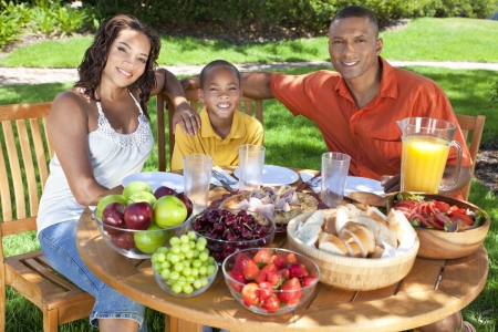 A happy, smiling African American family, mother father & son eating healthy food at a table outside, the father is serving a orange juice to the boy. Stock Photo - 20880712