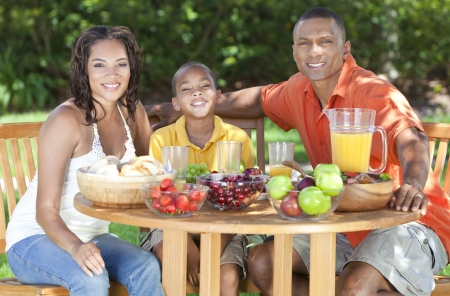 happy black family: An attractive happy, smiling African American family of mother, father, son, man woman, boy child eating healthy food at a picnic table outside Stock Photo