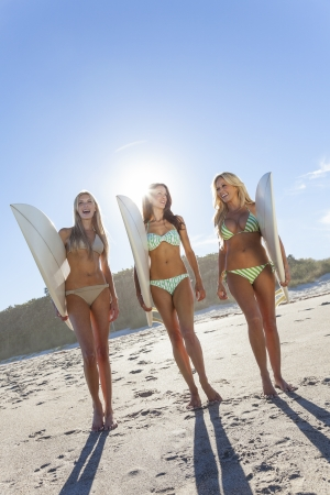 blue bikini: Three Beautiful young women surfer girls in bikinis with white surfbords at a beach Stock Photo