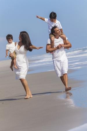Een gelukkige familie van moeder, vader, ouders en twee jongen zoon kinderen, spelen en plezier in de golven van een zonnig strand