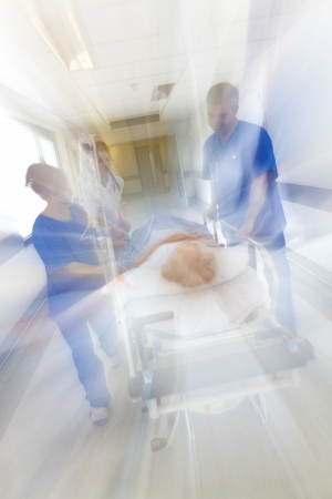 pushed: A motion blurred photograph of a senior female patient on stretcher or gurney being pushed at speed through a hospital corridor by doctors & nurses to an emergency room