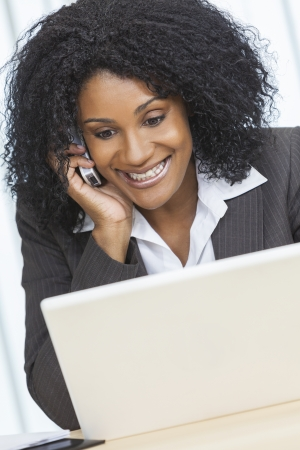 Portrait of a beautiful middle aged African American woman or businesswoman smiling using a cell phone and laptop computer looking happy and surprised photo
