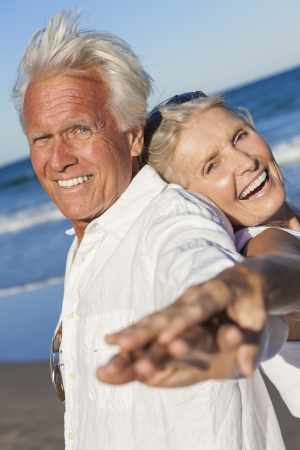 Happy senior man and woman couple together laughing back to back by blue sea on a deserted tropical beach with bright clear blue sky Standard-Bild