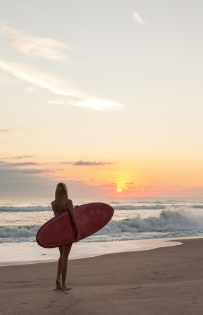 Rear view of a beautiful young woman surfer girl in bikini with red surfboard at a beach sunset or sunrise