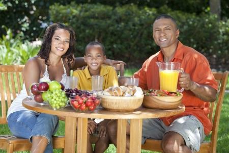 외부 테이블에 건강한 음식을 먹고 행복, 웃는 아프리카 계 미국인 가족, 어머니 아버지 및 아들, 아버지는 소년에게 오렌지 주스를 제공하고있다.