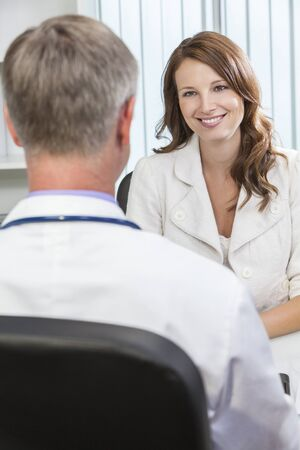doctor appointment: Happy smiling middle aged woman patient or colleague meeting consultation appointment with male doctor in hospital or surgery office