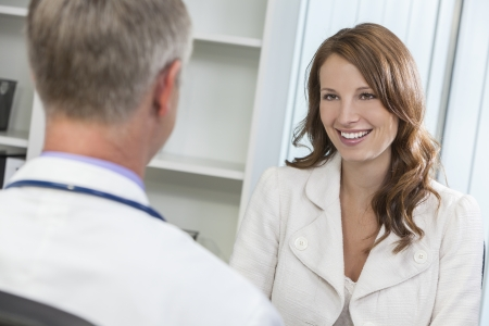 doctor's appointment: Happy smiling middle aged woman patient or colleague meeting consultation appointment with male doctor in hospital or surgery office