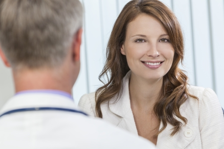 Happy smiling middle aged woman patient or colleague meeting consultation appointment with male doctor in hospital or surgery office