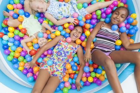 ni�as jugando: Grupo interracial de las ni�as, los ni�os americanos rubios y africanas que se divierten riendo jugando bolas de pl�stico de colores en una piscina de bolas Foto de archivo