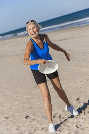 Fit and healthy senior woman playing with frisbee on a deserted beach by the sea photo