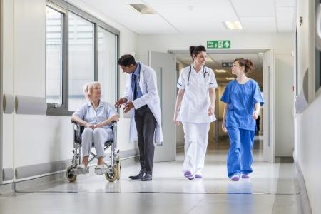 Dokters & verpleegkundige in het ziekenhuis corridor met senior vrouwelijke patiënt in de rolstoel met mannelijke Aziatische arts