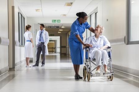 paciente: Mujer paciente de sexo femenino mayor en silla de ruedas sentado en el pasillo del hospital con la enfermera africana americana y m�dico