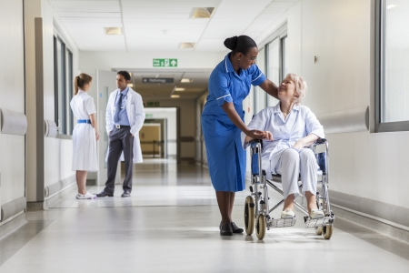 Senior vrouwelijke vrouw patiënt in een rolstoel zitten in het ziekenhuis gang met Afro-Amerikaanse vrouwelijke verpleegkundige en arts Stockfoto