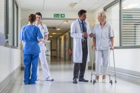 남자 간호사는 의사 및 고위 여성 환자와 병원 복도에서 들것 들것 침대를 밀어 스톡 콘텐츠