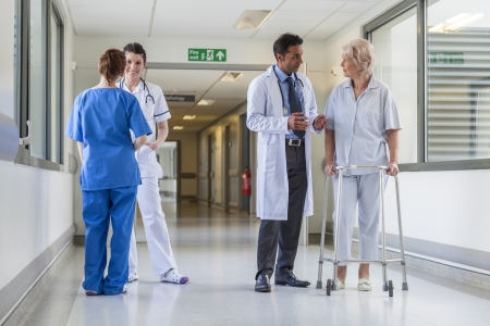 paciente en camilla: Enfermero empujando camilla cama camilla en el pasillo del hospital con los m�dicos y los pacientes de sexo femenino mayor Foto de archivo