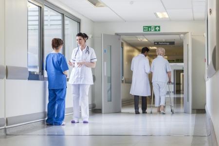Hospital corridor with doctors, nurses & senior female patient