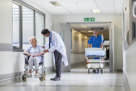 empujando: Enfermero empujando camilla cama camilla en el pasillo del hospital con el doctor y paciente de sexo femenino mayor