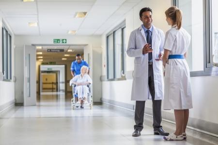 아시아, 인도 남성 의사 및 배경 및 수석 여성 휠체어 환자와 아프리카 계 미국인 간호사가 병원 복도에서 여성 간호사