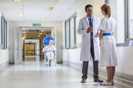 Asian Indian male doctor & female nurse in hospital corridor with a & senior female wheelchair patient and African American nurse in background Standard-Bild
