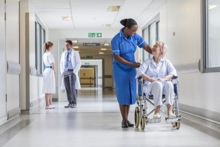 Senior female woman patient in wheelchair sitting in hospital corridor with African American female nurse doctor and nurse in background Stock Photo