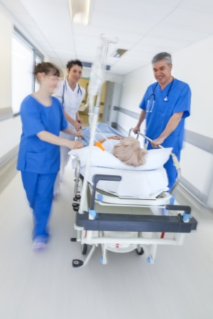 A motion blurred photograph of a senior female patient on stretcher or gurney being pushed at speed through a hospital corridor by doctors & nurses to an emergency room photo