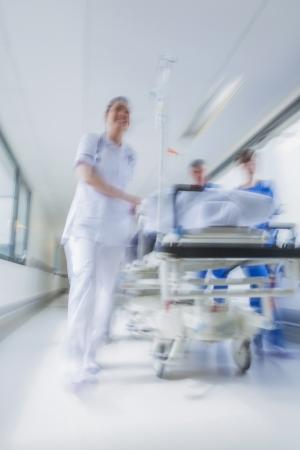 들것 또는 응급실 의사 및 간호사가 병원 복도를 통해 속도로 밀려 들것에 환자의 모션 흐리게 사진 스톡 콘텐츠