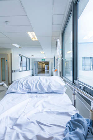 bereavement: Bereavement, death or loss concept shot of empty bed, gurney or stretcher with drip in hospital corridor