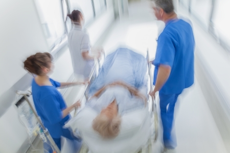 A motion blurred photograph of a senior female patient on stretcher or gurney being pushed at speed through a hospital corridor by doctors & nurses to an emergency room Banco de Imagens - 23049928