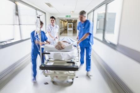 들것 또는 응급실 의사 및 간호사가 병원 복도를 통해 속도로 밀려 들것에 고위 여성 환자의 모션 흐리게 사진