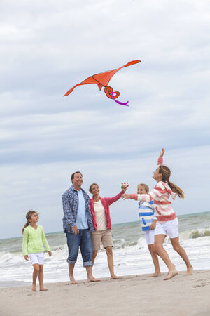Happy family mother, father, daughter, parents and female girl children flying a red kite, playing & laughing on a beach  photo