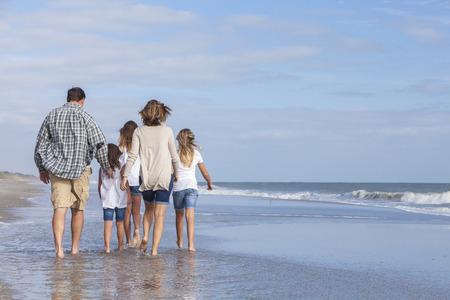 家族の母、父、娘、両親と海のビーチを歩いて女性女の子子供の背面図 写真素材