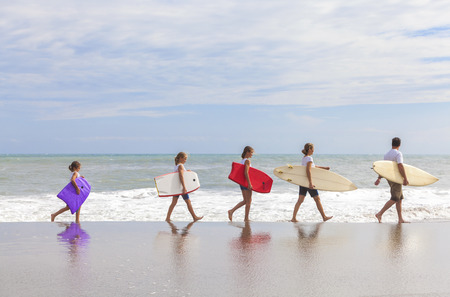 Rear view of family mother, father, daughter, parents and female girl children going surfing with surfborards on a sunny vacation day