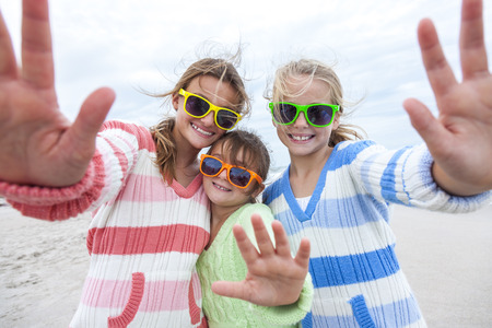 Female girl children having fun wearing sunglasses & waving to a camera taking selfie photograph on a beach photo