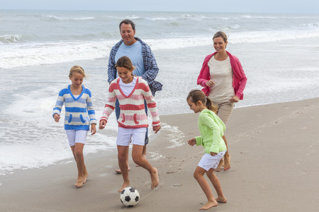 Family mother, father, daughter, parents and female girl children having fun playing football or soccer on a beach  photo