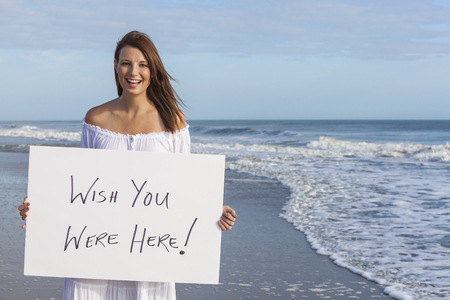 pink floyd: Happy smiling beautiful girl young woman on sunny vacation beach holding white card saying Wish You Were Here Stock Photo