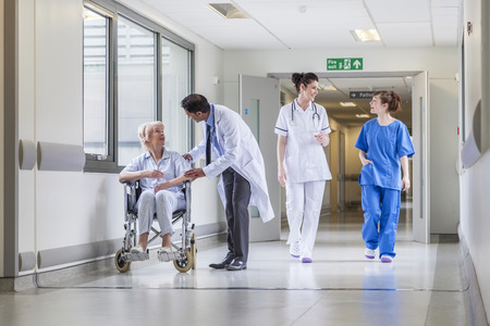 Senior female woman patient in wheelchair sitting in hospital corridor with Asian Indian male doctor and female nurse colleagues Foto de archivo
