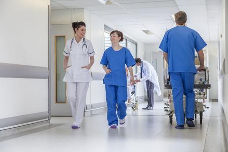 Male nurse pushing stretcher gurney bed in hospital corridor with male & female doctors & nurses & senior female patient in a wheelchair Standard-Bild