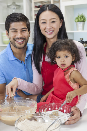 Asian Chinese family, man & woman parents and young girl child daughter cooking, baking, making cakes in home kitchen photo