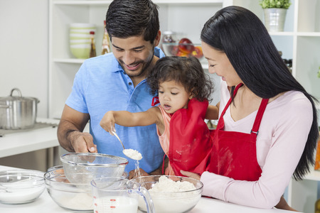 Asian Chinese family, man & woman parents and young girl child daughter cooking, baking, making cakes in home kitchen